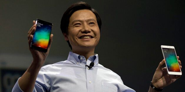 Lei Jun, chairman of Chinese smartphone maker Xiaomi, holds up the latest models of the Xiaomi Note at...