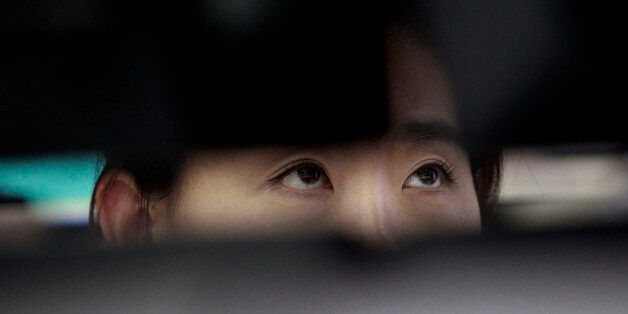 A currency trader watches monitors at the foreign exchange dealing room of the Korea Exchange Bank headquarters...
