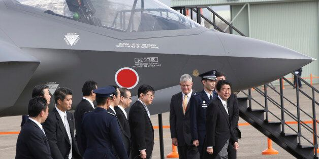 FILE - In this Oct. 26, 2014 file photo, Japanese Prime Minister Shinzo Abe, right, walks by a mock-up...