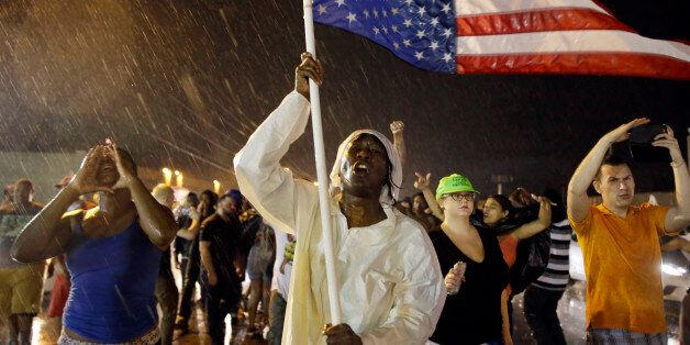 Protesters march in the rain, Sunday, Aug. 9, 2015, in Ferguson, Mo. Sunday marks one year since Michael...