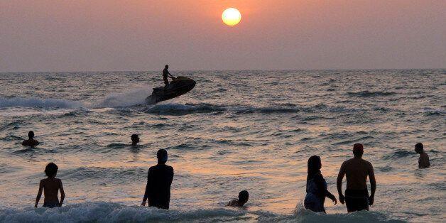 People enjoy a sunset swim at a public beach in Dubai, United Arab Emirates, Thursday, Sept. 6, 2012....