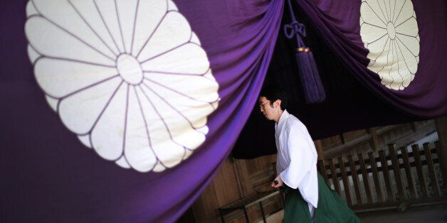 A Shinto priest walks at Yasukuni Shrine during an annual autumn festival in Tokyo, Friday, Oct. 17,...
