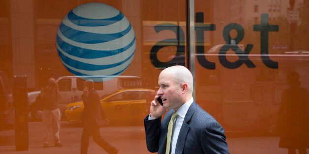 A man using a mobile phone walks past an AT&T store, Tuesday, June 23, 2015 in New York. (AP Photo/Mark