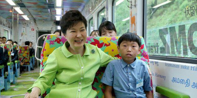 박근혜 대통령이 5일 강원도 철원군 백마고지역으로 가는 경원선 열차에서 탈북자 자녀 이정민군과 함께 앉아