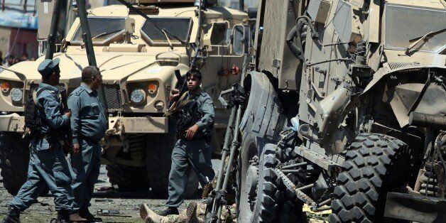 FILE - In this Tuesday, June 30, 2015 file photo, Afghan security personnel investigate site of a suicide...