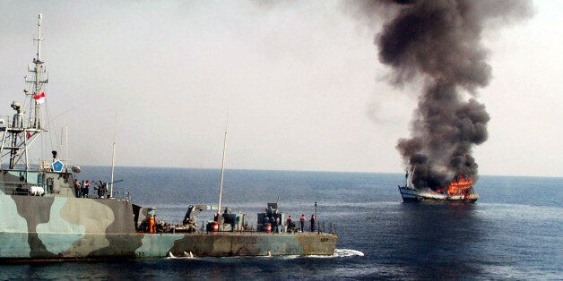 Smoke billows from M.V. Karunia Laut-1, left, as it caught on fire after being shot by an Indonesian...
