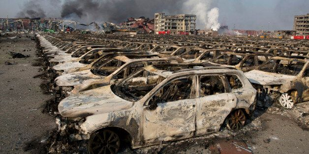 Smoke billows from the site of an explosion that reduced a parking lot filled with new cars to charred...