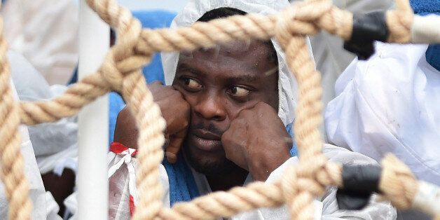 A migrant shelters from rain as he waits to disembark from Italian Coast Guard ship Oreste Corsi, at...