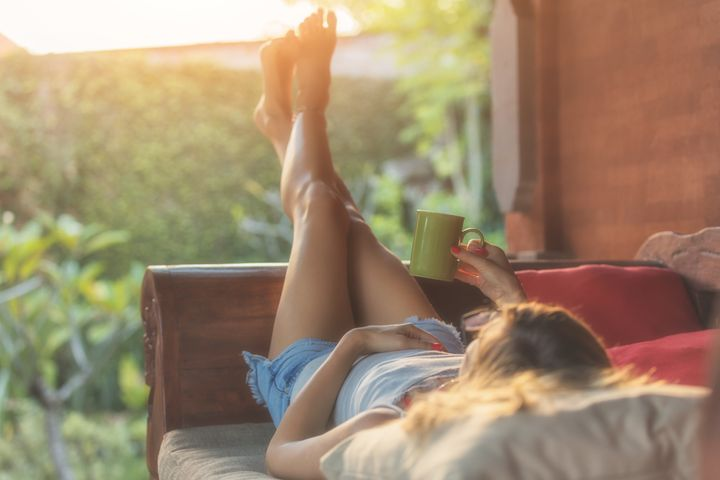 Girl enjoying morning coffee on the porch.