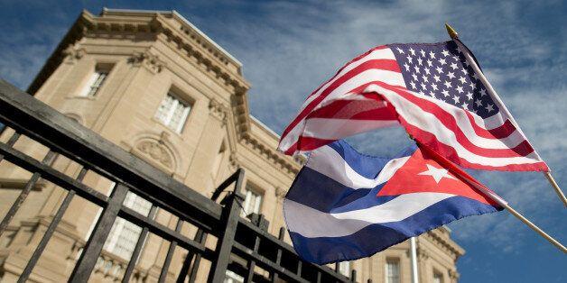 Edwardo Clark, a Cuban-American, holds an American flag and a Cuban flag as he celebrates outside the...