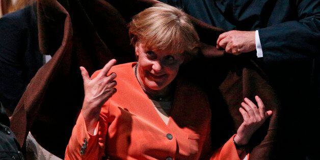 Russian President Vladimir Putin, second right, covers Germany's Chancellor Angela Merkel warm blanket...
