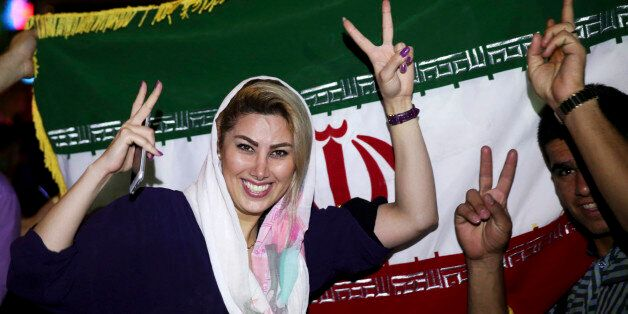 An Iranian woman shows the victory sign as people celebrate on a street following a landmark nuclear...