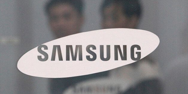 Employees walk past a logo of Samsung Group at the head office of Samsung C&T Corp. in Seoul, South Korea,...