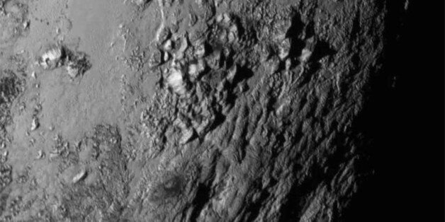 This Tuesday, July 14, 2015 image provided by NASA on Wednesday shows a region near Pluto's equator with...