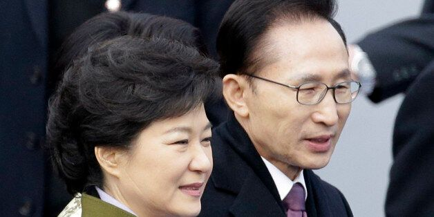 FILE - In this Feb. 25, 2013 file photo, South Korea's outgoing President Lee Myung-bak, right, walks...
