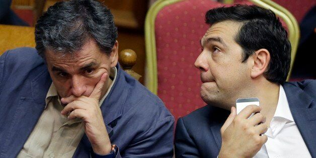 Greece's Prime Minister Alexis Tsipras, right, and Finance Minister Euclid Tsakalotos react as they attend...