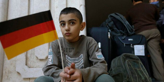 A Syrian refugee holds a German flag at the International Organization for Migration office as he waits...