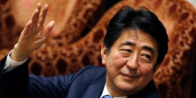 Japanese Prime Minister Shinzo Abe raises a hand to answer a lawmaker's question during a parliament...