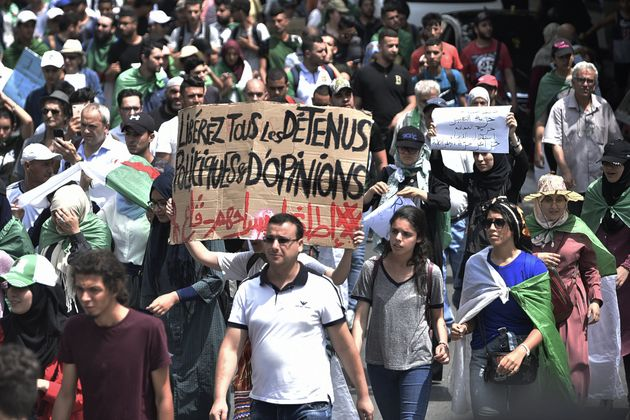 Algerian demonstrators carry a placard calling for the release of detainees as they take part in a protest...