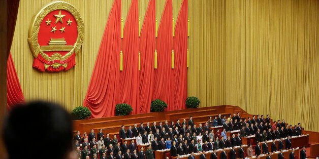 Delegates stand to listen to the Chinese national anthem during the opening session of the National People's...