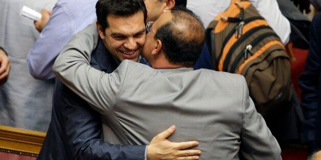 Greece's Prime Minister Alexis Tsipras is greeted by a lawmaker of his Syriza party after a parliament...