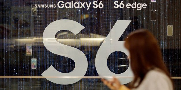 A woman walks by the advertisement of Samsung's Galaxy S6 smartphone outside its showroom in Seoul, South...