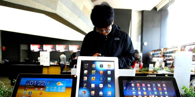 A student uses a mobile phone near the Samsung Electronics' new tablet Galaxy Tab 10.1 with Apple's white...