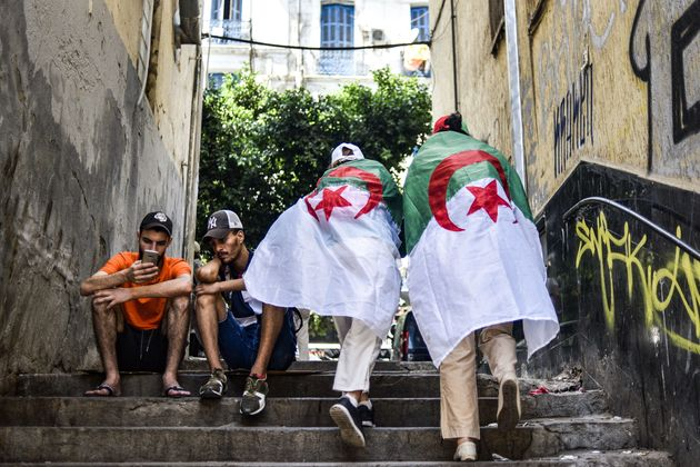 Women draped in Algerian national flags ascend a staircase along a street as protesters take part in...