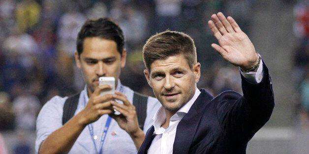 Newly acquired Los Angeles Galaxy midfielder Steven Gerrard, right, waves to the fans as he is introduced...