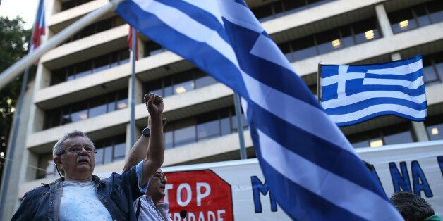 People sing a protest song as others wave Greek flags during a rally in support to the Greek government...