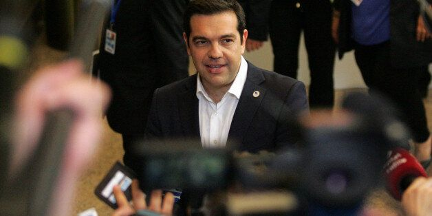 Greek Prime Minister Alexis Tsipras, center, speaks with the media after an emergency summit of eurozone...