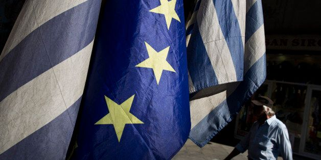 A man walks past a European and Greek flags in central Athens, on Tuesday, June 30, 2015. The European...
