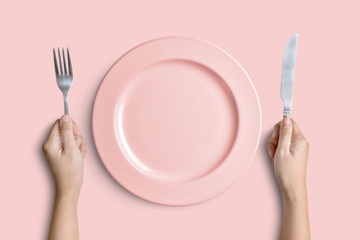 Dinner place setting. A pink plate with silver fork and knife isolated on pink background with clipping path