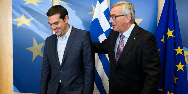 Greek Prime Minister Alexis Tsipras, left, is greeted by European Commission President Jean-Claude Juncker...