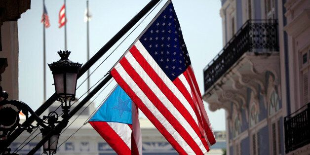 The U.S. and Puerto Rico flags wave in front of the governor's mansion in Old San Juan, Puerto Rico,...