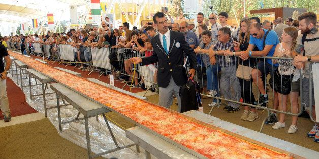 Judge of the Guinness World Records Lorenzo Veltri checks the length of a pizza at the Expo 2015 world's...