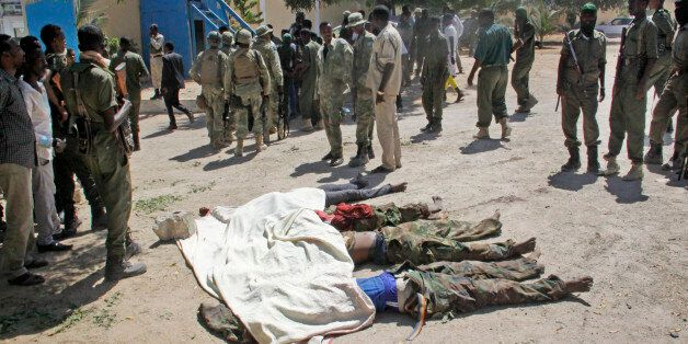 Somali soldiers look at the bodies of suspected attackers after a car bomb that was detonated at the...