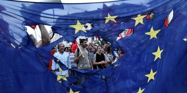 Members of left wing parties burn a European Union flag during a protest in the northern Greek port city...