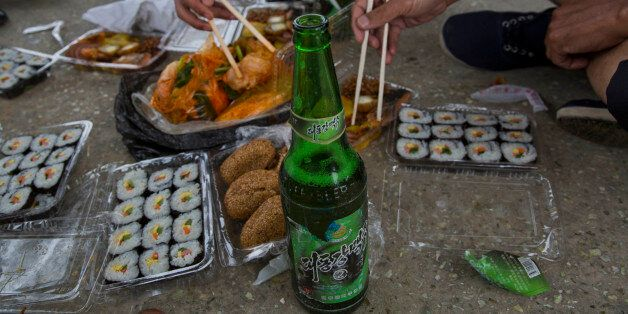 In this June 16, 2014 photo, North Korean men share a picnic lunch and North Korean-brewed and bottled...