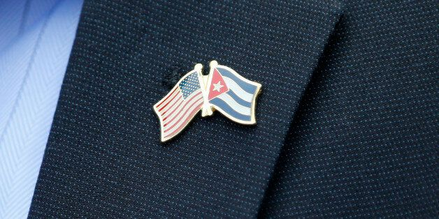 A member of the U.S. Senate delegation wears a crossed flag pin representing the US and Cuban national...