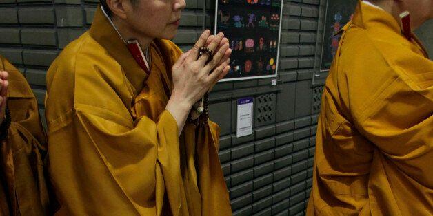 Japanese Buddhist nuns greet Tibetan spiritual leader the Dalai Lama upon his arrival for a Buddhist...