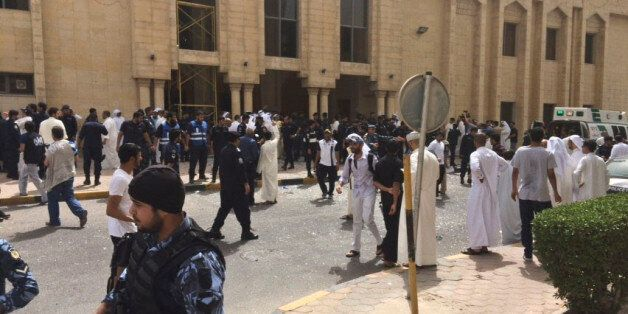 Security forces, officials and civilians gather outside of the Imam Sadiq Mosque after a deadly blast...