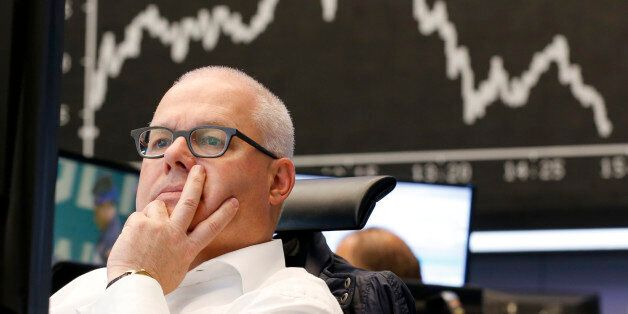 A broker sits under he curve of the German stock index DAX at the stock market in Frankfurt, Germany,...