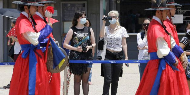 Tourists wearing masks as a precaution against MERS, Middle East Respiratory Syndrome, virus watch a...