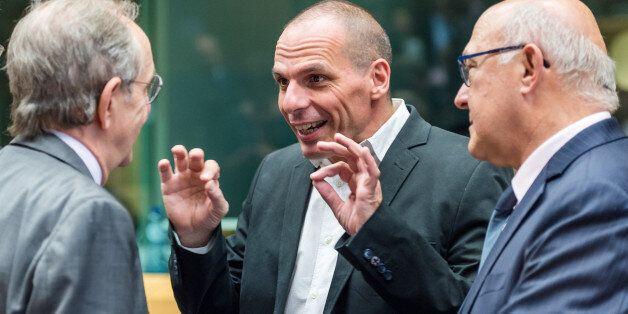 Greek Finance Minister Yanis Varoufakis, center, gestures as he talks with Italian Finance Minister Pier...
