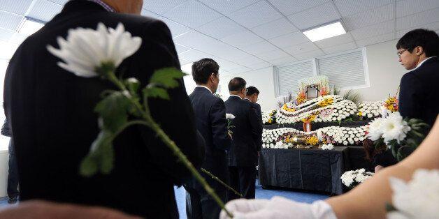 2일 오전 광주시청 1층에 차려진 분향소에서 동료 공무원들이 전날 중국 지린성에서 발생한 버스 추락 사고로 숨진 광주시청 공무원 김철균 지방공업사무관를 추모하며 헌화하고 있다.