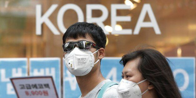 A couple wears masks as a precaution against the Middle East Respiratory Syndrome (MERS) virus as they...