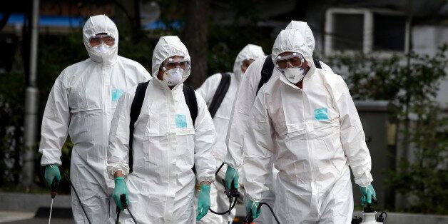 Workers wearing protective gears arrive to spray antiseptic solution as a precaution against the spread...