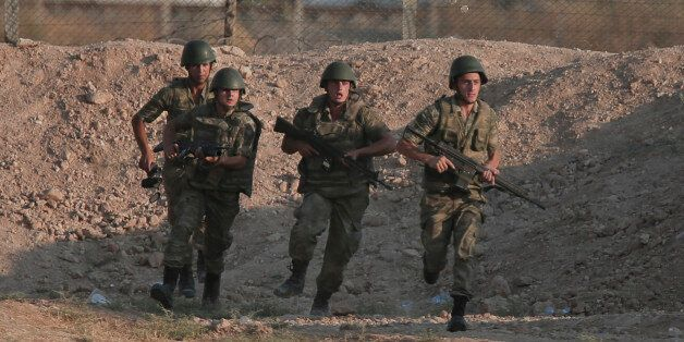 Turkish soldiers run to their new positions at the Syria border in Akcakale, southeastern Turkey, Monday,...