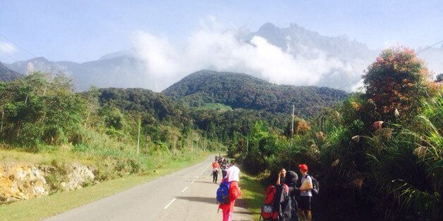 Tourists walk away from Mount Kinabalu hours after a magnitude 5.9 earthquake shook the area in Kundasang,...